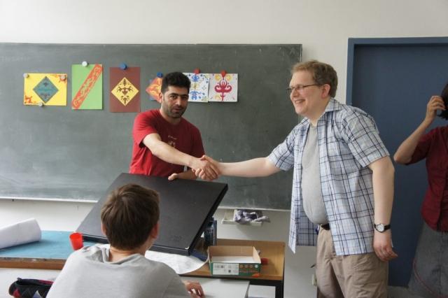 Herr Daling überreicht Ahmed eine Mappe für seine Kunstwerke